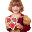 Beautiful little girl holding gingerbread heart - Стоковая фотография