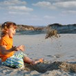 Stock Photo: Happy little girl playing in sand