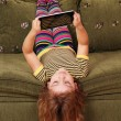 Little girl lying upside down on bed and play with tablet — Stock Photo #13639905