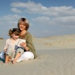 Mother and daughter play with tablet in desert — Stock Photo #13639958