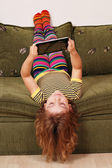Little girl lying upside down on bed and play with tablet — Stock Photo