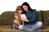 Teenage and little girl playing with tablet pc — Stock Photo