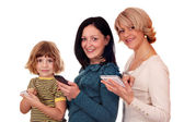 Little girl teenage girl and woman with phones and tablet pc — Stock Photo