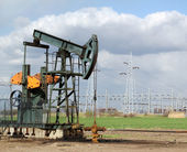 Oil field with pumpjack — Stock Photo