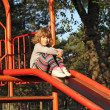 Little girl sitting on slide — Stock Photo