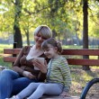 Mother and daughter sitting in park and play with tablet — Stock Photo