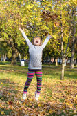 Little girl jump and throws leaves — Stock Photo