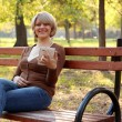 Beautiful woman sitting in park and play with tablet - Stock Photo