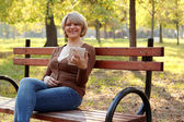Beautiful woman sitting in park and play with tablet — Stock Photo