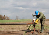 Oil worker closes the valve — Stock Photo