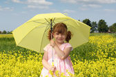 Niña con sombrilla amarilla — Foto de Stock