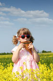 Little girl standing in yellow flower field and play pan pipe — Stock Photo