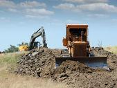Bulldozer en graafmachine op wegenbouw — Stockfoto