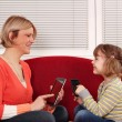 Mother and daughter with tablet and smart phone - Stock Photo