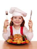 Petite fille cuisinier avec poulet grillé — Photo