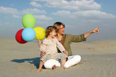 Happy mother and daughter with colorful balloons — Stock Photo
