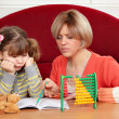 Unhappy daughter and mother doing homework - Stok fotoğraf
