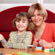 图库照片: Happy mother and daughter play with plasticine
