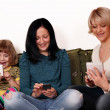 Happy mother and daughters playing with smart phones and tablet — Stok fotoğraf