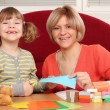 Stock Photo: Happy little girl cutting with scissors
