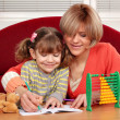 Mother and daughter doing homework family scene — Stock Photo