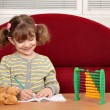 Happy little girl doing homework — Stock Photo