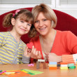 Foto Stock: Happy mother and daughter play with plasticine and make heart