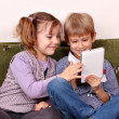 Stock Photo: Happy little girl and boy playing with tablet pc