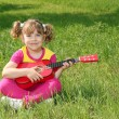 Happy little girl with guitar sitting on grass - Stock Photo