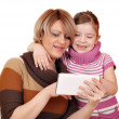 Mother and daughter play with tablet pc on white  — Stock Photo