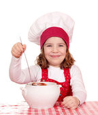 Happy little girl cook with soup — Stok fotoğraf