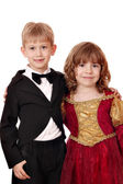 Boy in tuxedo and little girl in golden red dress portrait — Stock Photo