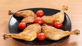 Chicken drumstick und tomaten auf schwarzem teller — Stockfoto