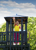 Happy little girl on wooden tower playground — Stock Photo
