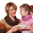 Happy mother and daughter play with tablet pc on white — Stockfoto