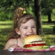 Hungry little girl eat big sandwich in park — Stock Photo