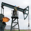 Oil worker stands at the pump jack — Stock Photo #23289386