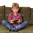 Boy sitting on bed and play video game — Stock Photo #23792103