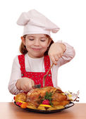 Little girl cook eat roasted chicken — Stock Photo