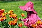Little girl smell tulip flower spring scene — Stock Photo