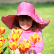 Little girl and tulip flowers garden — Stock Photo #24401453