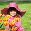 Beautiful little girl with tulip flowers portrait — Stock Photo
