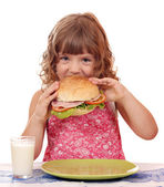 Hungry little girl eating sandwich — Stock Photo