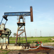 Stock Photo: Oilfield with pump jack and pipeline