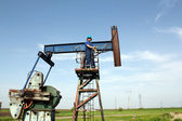 Oil worker and pump jack industry scene — Stock Photo