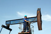 Oil worker with sunglasses standing at pump jack — Stock Photo