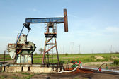 Oilfield with pump jack and pipeline — Stock Photo