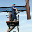 Stock Photo: Oil worker in blue uniform standing at pump jack