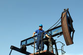 Oil worker standing on pump jack — Stock Photo
