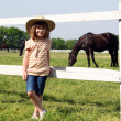 Little girl on horse farm — Stock Photo